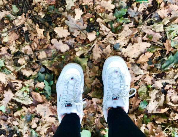 feet standing in autumn leaves
