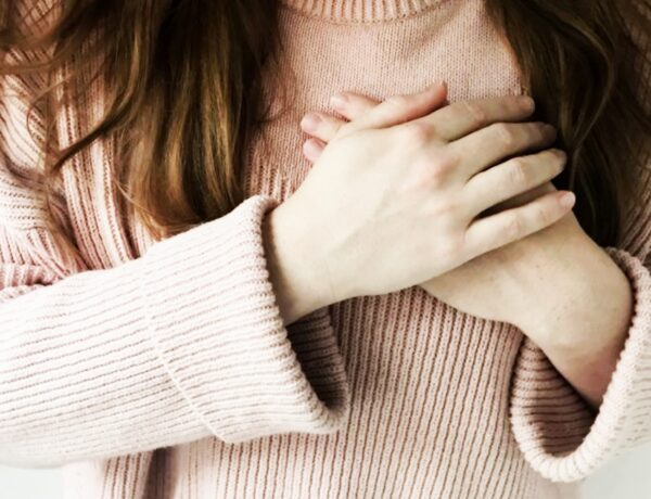 a woman clutching her hands over her heart